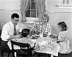 1950s FAMILY SITTING AT KITCHEN TABLE HAVING BREAKFAST