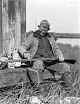 1920s 1930s SENIOR MAN SITTING ON BENCH CLEANING DUCK HUNTING SHOTGUN