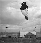 1950s MAN TIGHTROPE WALKER JUMPING THROUGH HOOP APPEARS SUSPENDED IN AIR UPSIDE DOWN