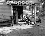 1930s 1940s FARM WOMAN WITH SIX CHILDREN ON PORCH OF CLAP BOARD FARM HOUSE POOR APPALACHIA DEPRESSION WASHTUB