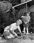 1960s BOY HELPING GRANDMOTHER PLANT FLOWERS IN GARDEN