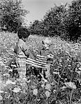 1970ER JAHRE PAAR BOYS EINE WEIßE EIN SCHWARZ SPANIER IM BEREICH DER QUEEN ANNE'S LACE AMERIKANISCHE FLAGGE HÄLT STÄNDIGEN