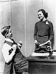 1940s TEEN YOUNG COUPLE BOY AT DESK AS BUSINESSMAN GIRL POLKA DOT DRESS STANDING AS SECRETARY SCHOOL PAPER
