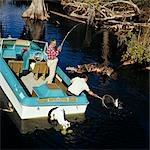 1970s TWO ELDERLY MEN FISHING IN CYPRESS SWAMP OFF BLUE WHITE MOTOR BOAT OUTBOARD ONE MAN ROD REEL OTHER NETS NET FISH