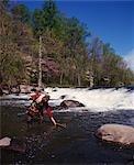 1970s MAN STANDING IN STREAM FLY FISHING SPRING SEASON WATER ROD REEL RED SHIRT WATERFALL ROCKS