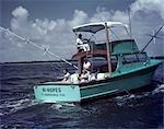 1950s MAN WOMAN FISHING OFF BACK STERN TURQUOISE CHARTER BOAT TWO MAN CREW WHITE BIMINI HI HOPES FT LAUDERDALE FL