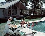 FAMILLE DES ANNÉES 1950 DE 4 JARDIN PISCINE MAISON MAMAN SERVANT DE NOURRITURE REPAS À TABLE PAR PAPA GRILL GARÇON FILLE ÉTÉ MOBILIER DE JARDIN