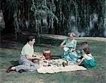 ANNÉES 1950 PÈRE MÈRE FAMILLE GARÇON FILLE 4 PIQUE-NIQUE SOUS L'ARBRE DE SAULE PLEUREUR DE LAC ÉTANG PLAID THERMOS LAIT NOURRITURE REPAS L'ÉTÉ