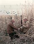 1950s 2 MEN HUNTERS TALL GRASS REEDS DUCK BLIND BROWN BEIGE HOT DRINK THERMOS SHOTGUNS DUCK DECOYS WATER LAKE AUTUMN