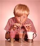 1950s 1960s BLOND BOY DRINKING THREE MILKSHAKES STRAWBERRY CHOCOLATE VANILLA THROUGH STRAWS AT SAME TIME
