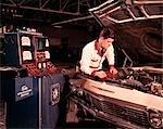 1960s MAN AUTO MECHANIC WORKING CAR ENGINE CONNECTED TO DIAGNOSTIC EQUIPMENT MEN MECHANIC CAR AUTOMOBILE