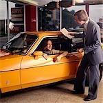 1970s SMILING WOMAN SITTING DRIVERS SEAT ORANGE CAR TALKING TO MAN AUTOMOBILE SALESMAN IN CAR DEALERSHIP