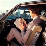 1970s MAN BUSINESSMAN SALESMAN USING POCKET CALCULATOR SITTING IN AUTOMOBILE