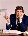 1970s MAN BUSINESSMAN BUSINESS DESK HOLDING PAPERS PAPERWORK BILLS SMILING FUNNY FACE EXPRESSION