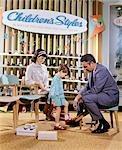 ANNÉES 1960 ANNÉES 1970 MÈRE VENDEUR REGARDANT FIT SHOES ON FILLE CHAUSSURES ARTICLE DE MAGASIN
