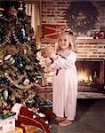 GIRL HOLDING DOLL BESIDE CHRISTMAS TREE