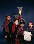 1960s GROUP MULTI-ETHNIC BOYS SINGING CHRISTMAS CAROLS UNDER LAMP POST