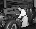 1940s MECHANIC LOOKING AT CAMERA WORKING UNDER HOOD OF CAR WEARING WORK SMOCK UNIFORM GARAGE