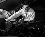 1950s MAN AUTOMOTIVE MECHANIC SERVICING CAR ENGINE