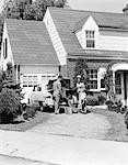 ANNÉES 1950 FAMILLE PÈRE MÈRE FILS IN FRONT DE SUBURBAN HOUSE CHARGEMENT VOITURE TRONC AVEC BAGAGES VALISE GOLF SAC VOYAGE VACANCES