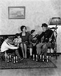 ANNÉES 1930 ANNÉES 1920 MÈRE & TROIS ENFANTS À L'ÉCOUTE DE GRAND-PÈRE EN GUERRE CIVILE UNIFORME TENANT FUSIL RACONTENT DES HISTOIRES DE GUERRE