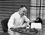 1940s DOCTOR SITTING AT DESK WRITING PRESCRIPTION