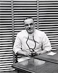 1940s PORTRAIT OF DOCTOR SITTING BEHIND DESK SMILING