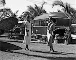 1930ER JAHREN 2 FRAUEN STEHEND REDEN ON TROPISCHEN RASEN IN FLORIDA-TRAILER PARK MIT EINEM AUTO REGENSCHIRM & STÜHLE