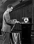 1950s 1960s STOCKBROKER READING TICKER TAPE IN FRONT OF STOCK EXCHANGE BOARD