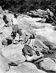 1920s TWO WOMEN SISTERS ON ROCKS BY CREEK TALKING HOLDING FOLDING CAMERA