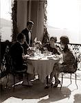 1920ER JAHRE GRUPPE ESSEN AM BALKON MIT KELLNER SERVIEREN WEIN