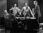 1930s FIVE OLDER BUSINESSMEN MEETING AROUND A DESK LISTENING TO A SIXTH YOUNGER MAN SPEAK