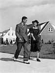1940s TEENAGE COUPLE WALKING ON SUBURBAN SIDEWALK