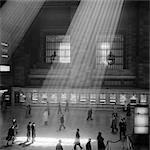 DES ANNÉES 1960 LA FOULE MARCHE PASSÉ LES RAYONS DU SOLEIL QUI TRAVERSE LE MAGNIFIQUE ATRIUM CAVERNEUX POÉTIQUE DRAMATIQUE DE GRAND CENTRAL STATION À NEW YORK CITY USA