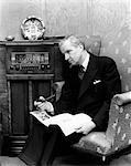 1940s ELDERLY MAN LEANING HEAD TOWARD RADIO PIPE IN HAND & NEWSPAPER IN LAP