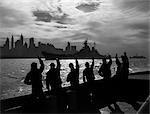 1950ER JAHRE SILHOUETTED MATROSEN DECK SCHIFF WINKEN SALUTE ZU ÜBERGEBEN USN SCHLACHTSCHIFF IN DER NACHT VOR DER SKYLINE VON NEW YORK