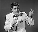 ANNÉES 1960 ANNÉES 1950 VESTE DE SMOKING BLANC HOMME TENIR MICRO SING PARLER LE GESTE AVEC LA MAIN INTERPRÈTE HÔTE EMCEE