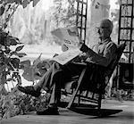 1970s ELDERLY MAN IN ROCKER READING NEWSPAPER ON PORCH