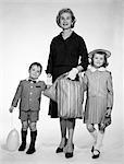 ANNÉES 1960 ANNÉES 1950 FEMME MÈRE DEUX ENFANTS GARÇON FILLE HOLDING MAINS CABAS HABILLÉ JUPE SHORT PANTS BALLON CHAPEAU FILLE FILS