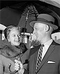 1960s SMILING DRESSED-UP ELDERLY COUPLE OUTSIDE UNDER LARGE UMBRELLA