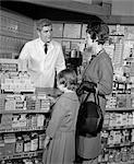 ANNÉES 1960 ANNÉES 1950 MÈRE FILLE COMPTOIR PHARMACIE PHARMACIEN DERRIÈRE LE COMPTOIR ÉTAGÈRES ENSEMENCÉS PRODUITS ASPIRIN MÉDECINE