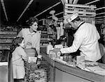 1960s MOTHER DAUGHTER UNLOAD GROCERY CART AT SUPERMARKET CHECKOUT COUNTER MAN CLERK CASHIER RINGS UP CASH REGISTER