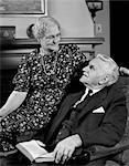 ANNÉES 1940 VIEUX COUPLE ASSIS DANS LE FAUTEUIL, REGARDANT LES UNS LES AUTRES