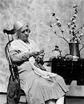 1920s ELDERLY WOMAN SITTING IN ROCKING CHAIR DARNING SOCK