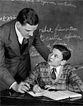1920s CLASSROOM MALE TEACHER HELPING BOY AT DESK - BLACKBOARD IN BACKGROUND