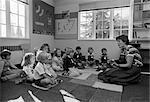 80ER JAHRE GRUNDSCHULE LEHRER SITZEN AUF BODEN MIT STUDENTEN SPIELEN GITARRE- & -GESANG