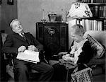 ANNÉES 1930 VIEUX COUPLE ASSIS DANS LE SALON À L'ÉCOUTE DE RADIO FEMME TRICOT HOMME AVEC JOURNAL EN TOUR