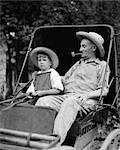 1930ER JAHREN FARM BOY & GROßVATER IN OVERALLS & STROH HÜTE SITZEN IN KLEINEN BUGGY