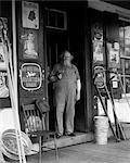 1930s ELDERLY BEARDED MAN IN OVERALLS SMOKING PIPE STANDING IN DOORWAY OF GENERAL STORE