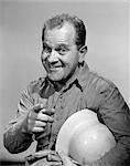 1960s SMILING PORTRAIT WORKMAN MAN HOLDING GLOVES WITH HARD HAT UNDER ARM POINTING INDEX FINGER